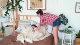 Le figlie sono caduto addormentato sul letto, la loro madre li copre di coperta, movimento lento