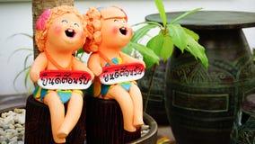 Le figure ceramiche bordi dei gemelli della tenuta dicono Fotografia Stock