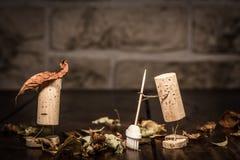 Le figure del sughero del vino, uomini di concetto due puliscono il fogliame Fotografia Stock