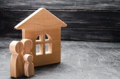 Le figure di legno della famiglia stanno vicino ad una casa di legno Il concetto di individuazione della casa nuova, muoventesi U immagini stock