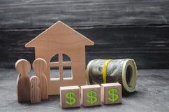 Le figure di legno della famiglia stanno vicino ad una casa, ad un prezzo da pagare ed ai soldi di legno Comprando e vendendo una fotografia stock libera da diritti