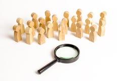 Le figure di legno della gente esaminano la lente d'ingrandimento Ricerca delle risposte alle domande, ricerche della casa o lavo fotografie stock