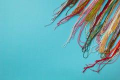 Le fil coloré multi utilisé pour tricoter des vêtements sur le fond rayé bleu image stock