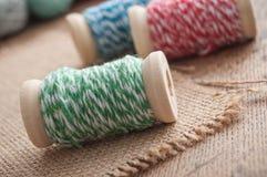 le fil de couture bobinent la bobine sur le fond en bois de table Image libre de droits