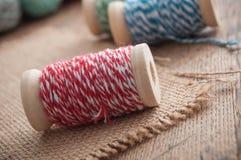 le fil de couture bobinent la bobine sur le fond en bois de table Photo libre de droits
