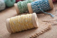 le fil de couture bobinent la bobine sur le fond en bois de table Images stock