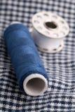 Le fil de couture roule sur le tissu Images libres de droits