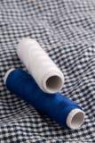 Le fil de couture roule sur le tissu Photo stock