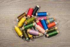 Le fil de couture tournoie sur un fond texturisé en bois Images libres de droits