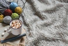 Le fil de laine dans le panier en métal de vintage, les vieux livres et le chocolat chaud dans une tasse en céramique sur le tiss Image stock