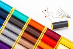 Le fil et l'aiguille de couture multicolores de concept de DIY sur le blanc soutiennent le GR Image libre de droits