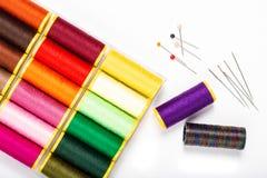 Le fil et l'aiguille de couture multicolores de concept de DIY sur le blanc soutiennent le GR Photographie stock