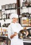 Le fil femelle de Mixing Egg With de chef battent dans la cuvette Images stock