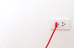 Le fil rouge avec la goupille plate a branché à la prise Images libres de droits