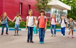 Le file dei bambini con gli Zaini si avvicinano alla camminata della scuola Fotografia Stock Libera da Diritti