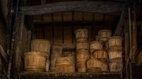 Le file dei barilotti di legno tradizionali del palo con i cerchi di bambù aspettano sulla via dietro un souce della soia che fa  Immagini Stock Libere da Diritti