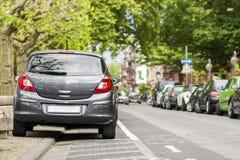 Le file delle automobili hanno parcheggiato sul bordo della strada in distretto residenziale Fotografie Stock