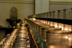 Le file delle candele votive si sono accese dai praticante nella cattedra cattolica fotografie stock