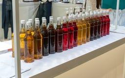 Le file di varietà hanno condito lo sciroppo in bottiglie di plastica sistemate su wh immagini stock