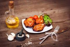 Le filet grillé juteux de porc a servi avec des tomates-cerises branche et laitue du plat blanc Fond : conseils en bois Plan rapp Photos libres de droits