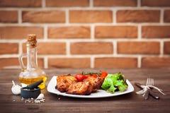 Le filet grillé juteux de porc a servi avec des tomates-cerises branche et laitue du plat blanc Fond : mur de briques Plan rappro Image libre de droits