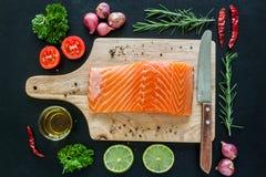 Le filet saumoné sur le conseil en bois avec garnissent prêt à cuisiner Image stock