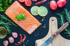 Le filet saumoné sur le conseil en bois avec garnissent prêt à cuisiner Photos stock