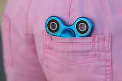 Le fileur populaire de personne remuante en métal bleu dans la poche arrière de jeans roses, de jouet de soulagement d'inquiétude Photos stock