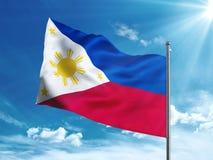 Le Filippine inbandierano l'ondeggiamento nel cielo blu Immagine Stock