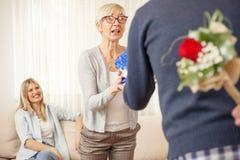 Le fils étonne sa mère et soeur avec des cadeaux image libre de droits