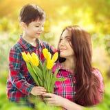 Le fils étreignant sa mère et lui donne des fleurs photos stock