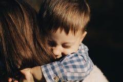 Le fils étreint la mère se trouvant sur l'épaule images libres de droits