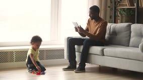 Le fils africain de père et d'enfant passent le temps dans le salon banque de vidéos