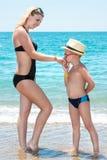 Le fils dans le chapeau, embrasse la main de la mère sur la côte image libre de droits