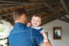 Le fils de bébé est aux mains de son père, les prises de garçon le parent par les épaules Photo stock