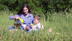 Le fils de maman mangent à un pique-nique dans la forêt clips vidéos