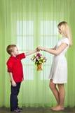 Le fils donne à sa mère aimée un panier des fleurs Concept de ressort des vacances de famille Jour du `s de femmes Photographie stock libre de droits