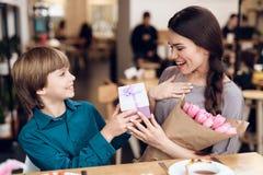 Le fils félicite sa mère sur le 8ème mars Image stock