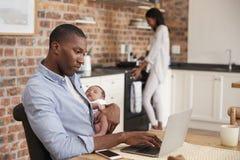 Le fils nouveau-né d'On Laptop Holds de père comme mère fait le repas Photos stock