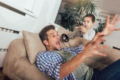 Le fils réveille son papa en jouant une trompette image stock