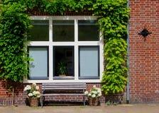 Le finestre olandesi della casa hanno circondato il banco dei fiori delle piante verdi fotografie stock libere da diritti
