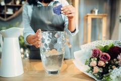Le fleuriste ajoute l'engrais à l'eau pour des fleurs photographie stock libre de droits