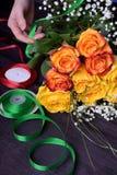 Le fleuriste compose un bouquet de roses et de fleurs jaunes et oranges de gypsophila image stock