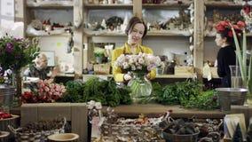 Le fleuriste dans un chemisier jaune apporte un bouquet dans un vase en verre et le met à côté des branches de sapin sur son lieu banque de vidéos