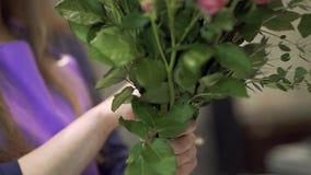 Le fleuriste de fille lie un bouquet des fleurs avec la ficelle Le fleuriste prépare un bouquet de fleurs pour la vente banque de vidéos
