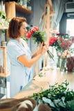 Le fleuriste féminin tient le fleuriste frais de roses rouges photos libres de droits