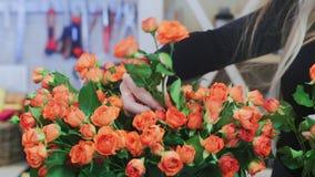 Le fleuriste prend une rose orange d'un bouquet banque de vidéos