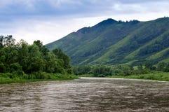 Le fleuve, les montagnes et le ciel obscurci. Images libres de droits