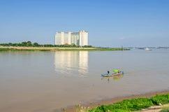 Le fleuve Tonle Sap avec un bateau et la rue de sève de Tonle avec l'hôtel de Sokha Image libre de droits