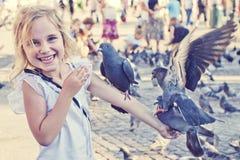 Le flicka med duvor på armen arkivfoton